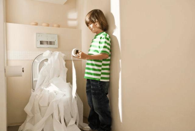 ילד משחק עם טישו בחדר השירותים
