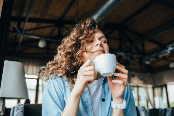 אישה שותה קפה מחייכת