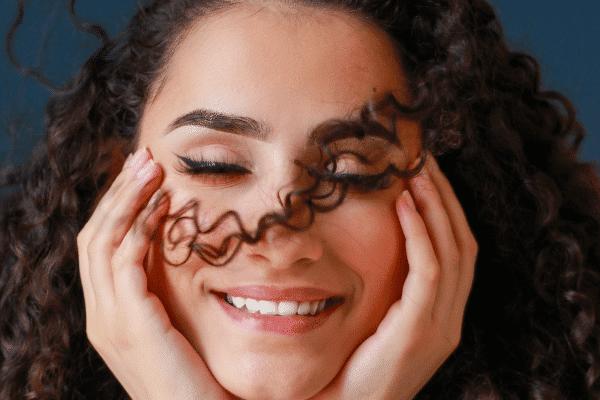 אישה מחייכת ועוצמת עיינים