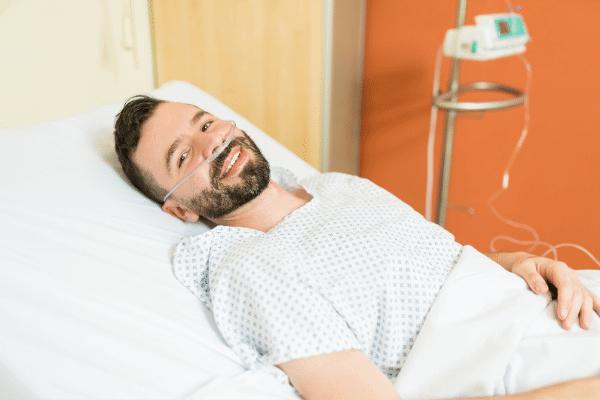 איש שוכב בבית חולים ומחייך